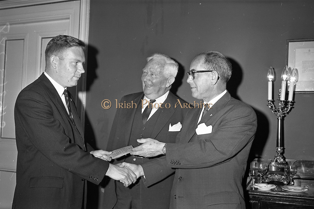 11/09/1962<br /> 09/11/1962<br /> 11 September 1962<br /> Ford International Fellowship Award for Ireland. In the Constitution Room of the Shelbourne Hotel, Dublin, 26 year old Sligo born Mr Patrick Joseph McGowan, M.Econ.Sc., of the Economic Division of the Central Bank of Ireland, who was leaving for the United States on the 13th as the Ford International Fellow for Ireland for 1962, was wished success in his studies by The U.S. Ambassador and members of An Bord Seolaireachtai Comalairte. Picture shows: Mr T.J. Brennan (right) Managing Director, Henry Ford and Son Ltd., Cork presenting the travel tickets to Mr Patrick McGowan, watched by His excellency Matthew McCloskey (centre) U.S. Ambassador to Ireland. Mr McGowan would leave from Cobh to spend a year at Princeton University, U.S.A. as Ford International Fellow for Ireland 1962.