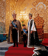 Mohammed Reza Shah Pahlavi (1919-1980) Shah of Iran 1941-1979, with his third wife Farah Diba and their son Reza in ceremonial dress in front of throne.