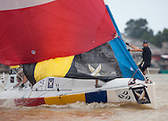 Iain Percy on the bow holding out the spinnaker. Monsoon Cup 2009. Kuala Terengganu, Malaysia. 3 December 2009. Photo: Sander van der Borch / Subzero Images
