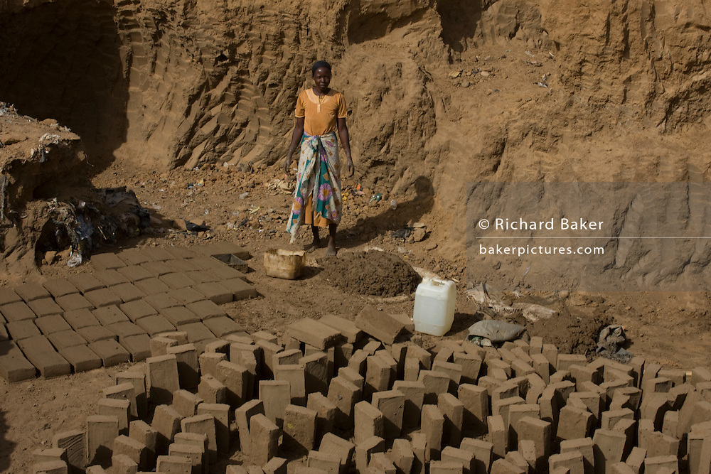 A Woman makes bricks for more stubstantial housing in the scorched barren dirt of the 4 sq km camp Abu Shouk refugee camp which is (disputedly) home to 38,000 displaced persons, on the outskirts of Al Fasher, North Darfur.