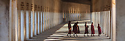 5 young Monks walk across long walkway with pillars and sunrise light coming through. Shwe Zi Gone Pagoda