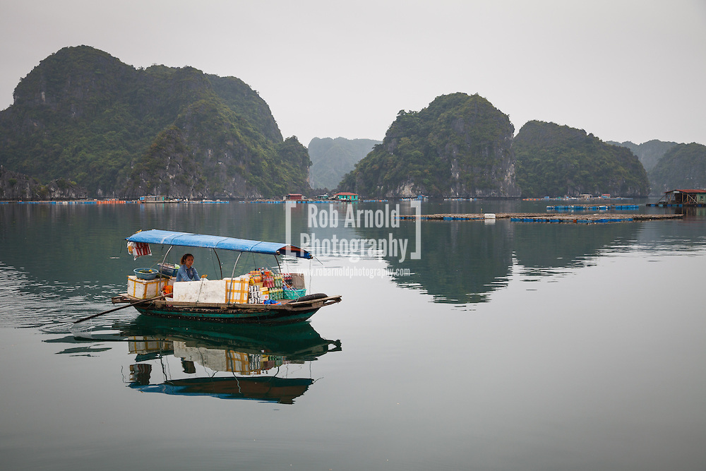 22/04/2013, Lan Ha Bay, Vietnam. A woman rowing her floating shop surrounded by the Limestone Karst formations in Lan Ha Bay, Vietnam. Photo by Rob Arnold