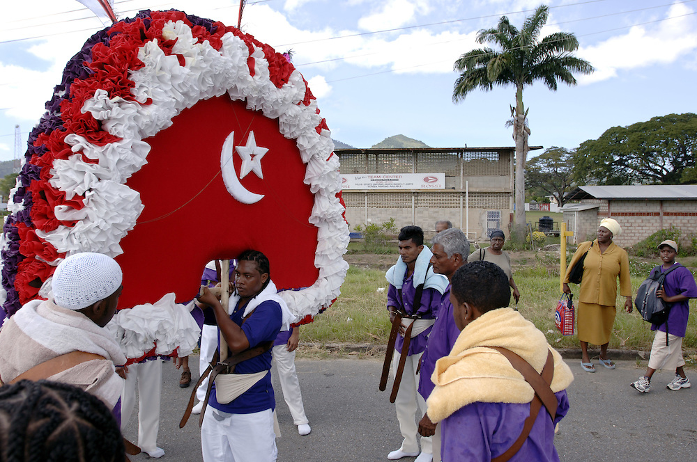 Trinidad & Tobago, Port of Spain St. James...Immigrants from India came to Trinidad in 1945 to work in the island's sugar cane plantations. They brought 'Hosay' to Trinidad, traditionally a muslim ceremony to mourn the death of Hussein and his brother Hassan. The modern Hosay parades in Trinidad are mostly held in St. James, a suburb of Port of Spain. Tassa drummers march in front of the multi-colored model mausoleums. On the last day of the ceremonies these replicas are destroyed and thrown into the ocean..Indische Einwanderer kamen vor 1945 nach Trinidad um auf den Zuckerrohrplantagen zu arbeiten Sie brachten die muslimische Tradition des 'Hosay' nach Trinidad, eine ehemehlige Trauerprozession um den Tod Hussein's und seines Bruders Hassan. Heute wird diese Prozession vor allem in Port of Spain's Vorort St. James aufrecht erhalten, wo Tassa Trommler vor den Replikas von Hassan's Grab laufen. Die Tadjahs werden am letzten Tag zerstoert und ins Meer geworfen.