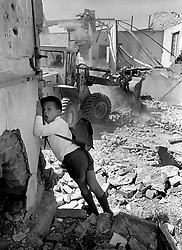 District 6 demolition 25.11.80.jpg<br /> A schoolboy watches as a bulldozer tears down buildings in District Six in 1980.<br /> Picture: Mike Mackenzie