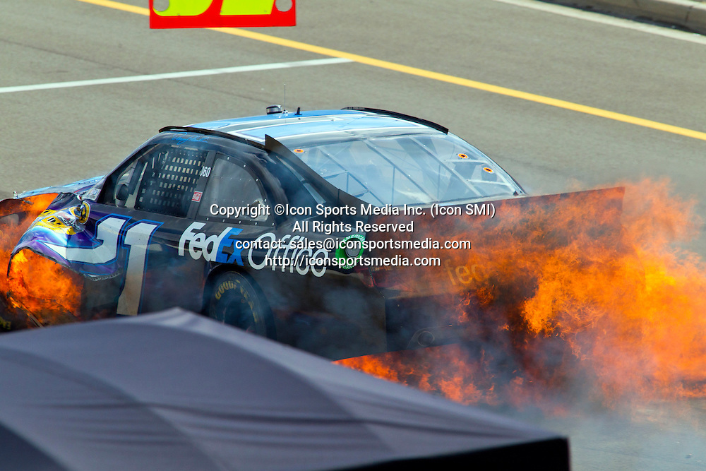 17 June 2012: Denny Hamlin, driver of the FedEx Express #11 Toyota, tries to pull his damaged and flaming vehicle towards his pit after colliding on turn four, during the NASCAR Sprint Cup Series Quicken Loans 400 at Michigan International Speedway in Brooklyn, MI.