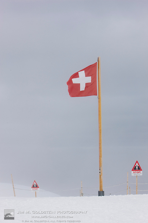 A weathered Swiss flag blowing in the wind atop an ice and snow covered landscape outside the Jungfraujoch station - Switzerland