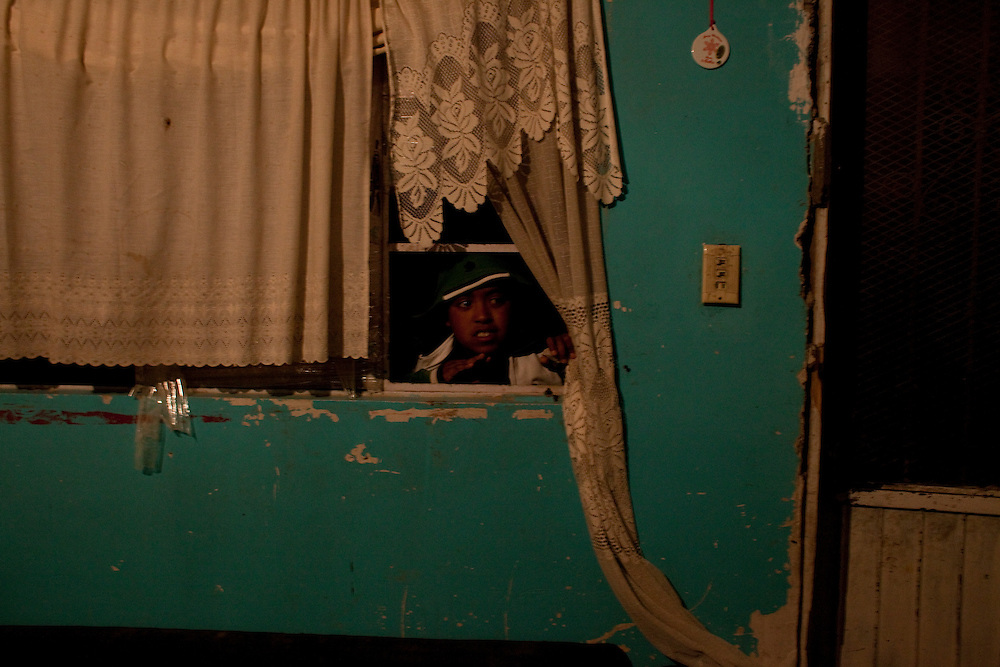 Christian David Reyes, 15, looks through the window of his friend's house in the Diaz Ordaz colonia in Ciudad Juarez, Chihuahua Mexico on May 1, 2010 as they get ready to go out to a night club. ..