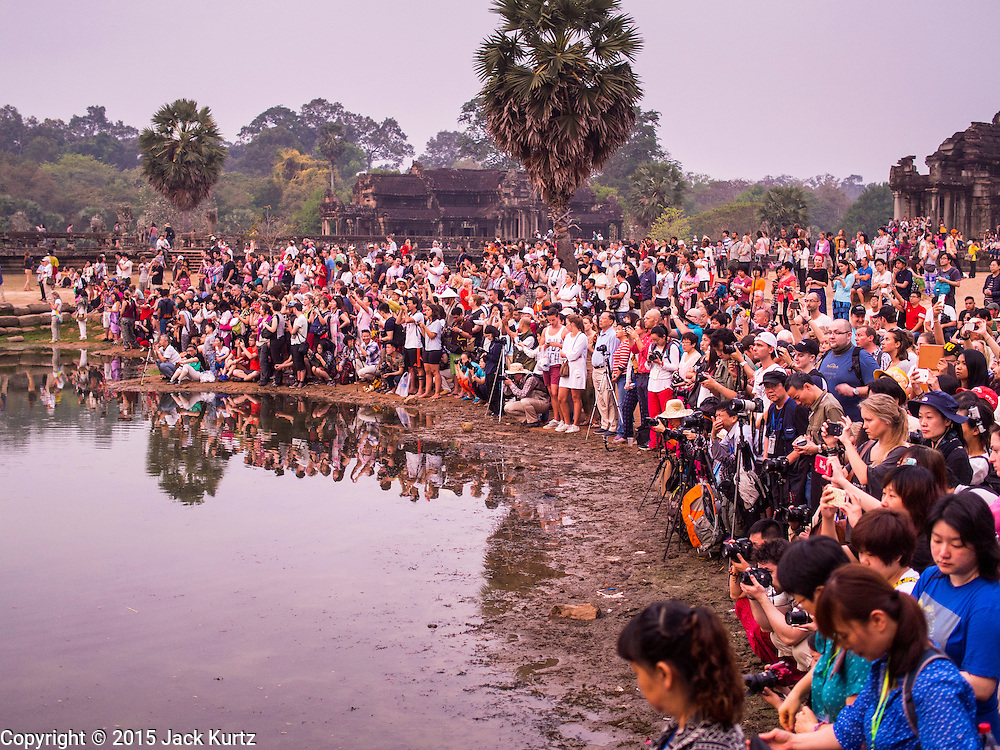 """14 MARCH 2105 - SIEM REAP, SIEM REAP, CAMBODIA: Tourists gathered around the reflecting pool in front of Angkor Wat wait for the sunrise. The area known as """"Angkor Wat"""" is a sprawling collection of archeological ruins and temples. The area was developed by ancient Khmer (Cambodian) Kings starting as early as 1150 CE and renovated and expanded around 1180CE by Jayavarman VII. Angkor Wat is now considered the seventh wonder of the world and is Cambodia's most important tourist attraction.   PHOTO BY JACK KURTZ"""