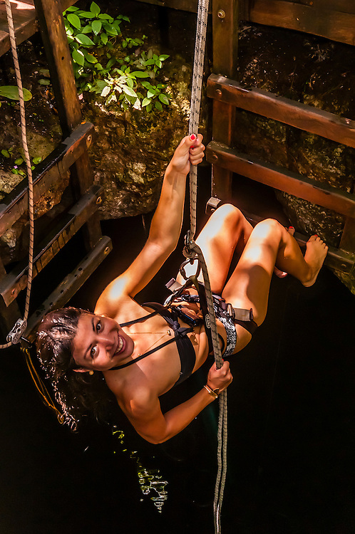 Woman rappelling into a cenote, a large limestone sinkhole which is part of the world's longest underwater river, Riviera Maya, Mexico