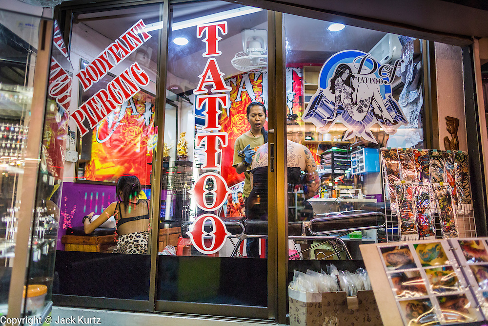 4 JUNE 2013 - BANGKOK, THAILAND:  A tattoo artist works in Def Tattoo in the Patpong Night Bazaar in Bangkok. Patpong was one of Bangkok's notorious red light districts but has been made over as a night market selling clothes, watches and Thai handicrafts. The old sex oriented businesses still exist but the area is now better known for its night shopping.      PHOTO BY JACK KURTZ