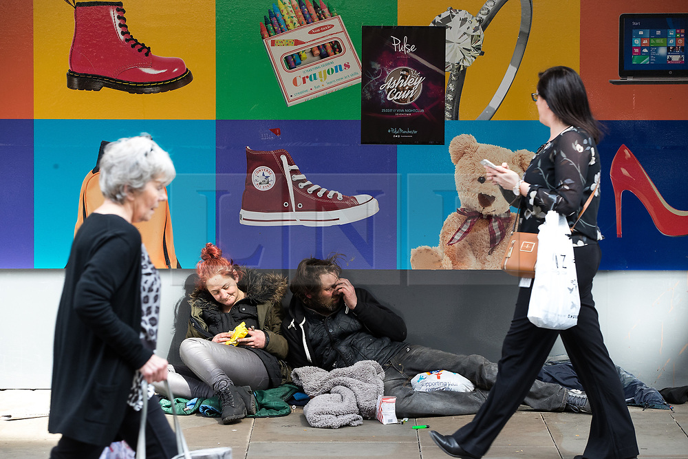 © Licensed to London News Pictures . 03/04/2017 . Manchester , UK . A man and a woman lie slumped against a shop window on Market Street in Manchester , as shoppers pass by . The city has experienced a growth in the number of people sleeping rough and emergency services report spikes in the need to tend to people high on Spice . Photo credit : Joel Goodman/LNP