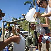 OCTOBER 25 - UTUADO, PUERTO RICO - <br /> Sgt. Gary Wyckoff helps residents fill containers with potable water at a station next to the Lago Dos Bocas in Utuado. Troops from Fort Bragg, NC, are using a water filtration system to purify the liquid.<br /> (Photo by Angel Valentin/Freelance)