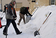 Four men work clearing snow from the parking lot of Worth a Second Look, a second hand store in Kitchener, Ontario, Canada. The men are working with Job Cafe, a casual work program of The Working Centre.