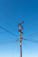 Several power lines and cables connectat the top of a PG&E power pole (telephone pole) against blue sky in the El Cerrito Hills of the  San Francisco Bay Area, California.