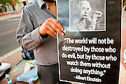 17 OCTOBER 2011 - PHOENIX, AZ:   A protester holds up a sign quoting Albert Einstein during the Occupy Phoenix protest Monday morning. About 40 people spent Sunday night on the sidewalks around the Cesar Chavez Plaza in Phoenix, AZ, the defacto headquarters of the Occupy Phoenix protest. Early Monday morning they got up to continue their chants and protests against Wall Street, the growing income gap between rich and poor in the US, and money in politics. Monday marks the third day of Occupy Phoenix.    PHOTO BY JACK KURTZ