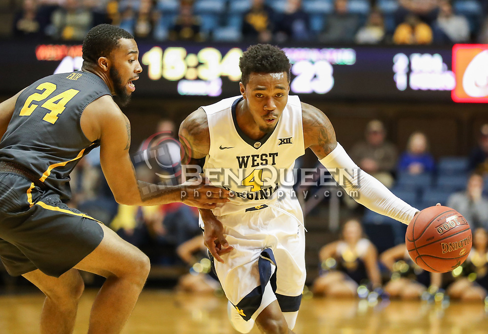 Dec 20, 2017; Morgantown, WV, USA; West Virginia Mountaineers guard Daxter Miles Jr. (4) drives past Coppin State Eagles guard Keandre Fair (24) during the second half at WVU Coliseum. Mandatory Credit: Ben Queen-USA TODAY Sports