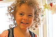 A biracial two year old girl has a happy smile and curly hair that stands out with backlighting in home setting, head and shoulder portrait