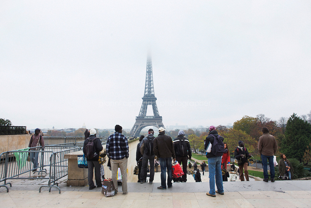 PARIS, FRANCE - 19 NOVEMBER 2014: African migrants sell miniature Eiffel Towers and keychains by the Eiffel Tower in Paris, France, on November 19th 2014.<br /> <br /> After crossing the Italian-French border, migrants take the train to Paris. Some stop in Paris, but the majority continues the journey to Calais (before arriving in London), while others go to countries such Germany, the Netherlands, and Sweden.