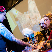 Manchester, UK - 5 August 2012: members of the jury examine a new tattoo during a contest at the Manchester Tattoo Show, one of the most popular conventions of the UK tattoo community.