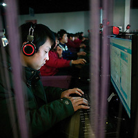 DEZHOU, JANUARY-12 , 2011 : a young man works on a computer in an internet cafe.