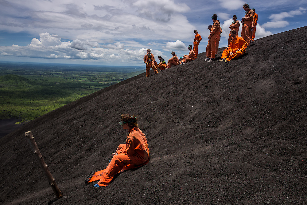LEON, NICARAGUA - SEPTEMBER 18, 2014: Kirstyn McCasey, 23, (left) prepares to board down Cerro Negro volcano. The jumpsuits are used for protective measures, because boarders reach high speeds of up to 95kilometers/hour and the rough surface at such high speeds can easily damage their skin. Guided tours are available from $29 USD to board down the volcano, located an hour outside of Leon. PHOTO: Meridith Kohut