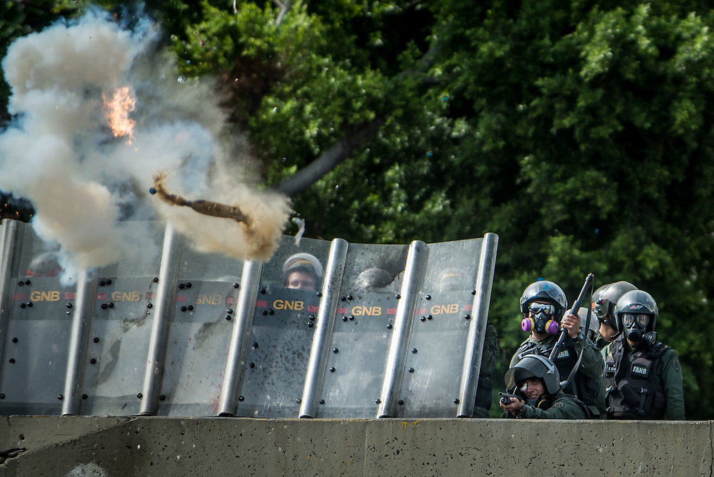 CARACAS, VENEZUELA - MAY 24, 2017: National Guard soldiers fire tear gas, rubber bullets and buckshot  at anti-government protesters. The streets of Caracas and other cities across Venezuela have been filled with tens of thousands of demonstrators for nearly 100 days of massive protests, held since April 1st. Protesters are enraged at the government for becoming an increasingly repressive, authoritarian regime that has delayed elections, used armed government loyalist to threaten dissidents, called for the Constitution to be re-written to favor them, jailed and tortured protesters and members of the political opposition, and whose corruption and failed economic policy has caused the current economic crisis that has led to widespread food and medicine shortages across the country.  Independent local media report nearly 100 people have been killed during protests and protest-related riots and looting.  The government currently only officially reports 75 deaths.  Over 2,000 people have been injured, and over 3,000 protesters have been detained by authorities.  PHOTO: Meridith Kohut
