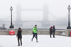 © Licensed to London News Pictures. 20/01/2013. London, UK. One of two comparison pictures showing the difference in weather between winter conditions in 2013 and 2014. The Thames path is covered by a blanket of snow on 20 January 2013. The Uk is experiencing unusually mild conditions for January. Photo credit : Vickie Flores/LNP