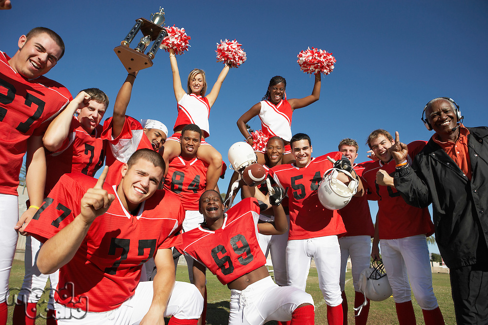 Football players cheerleaders and coach hoisting trophy portrait
