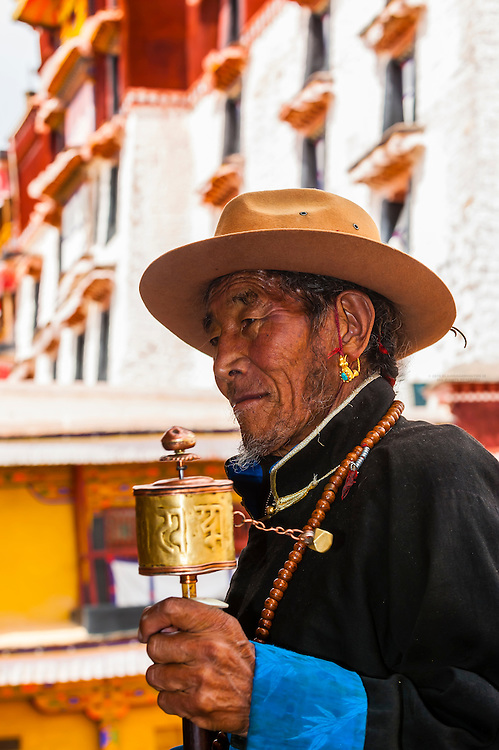 A Tibetan pilgrim spins a prayer wheel outside the Potala Palace (former residence of the Dalai Lama), Lhasa, Tibet, China.