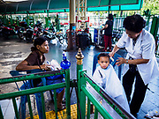 "11 APRIL 2017 - BANGKOK, THAILAND: Songkran travelers get free haircuts in Hua Lamphong train station during the Songkran travel period at Hua Lamphong train station in Bangkok. Songkran is the traditional Thai Lunar New Year. It is celebrated, under different names, in Thailand, Myanmar, Laos, Cambodia and some parts of Vietnam and China. In most places the holiday is marked by water throwing and water fights and it is sometimes called the ""water festival."" This year's Songkran celebration in Thailand will be more subdued than usual because Thais are still mourning the October 2016 death of their revered Late King, Bhumibol Adulyadej. Songkran is officially a three day holiday, April 13-15, but is frequently celebrated for a full week. Thais start traveling back to their home provinces over the weekend; busses and trains going out of town have been packed.     PHOTO BY JACK KURTZ"