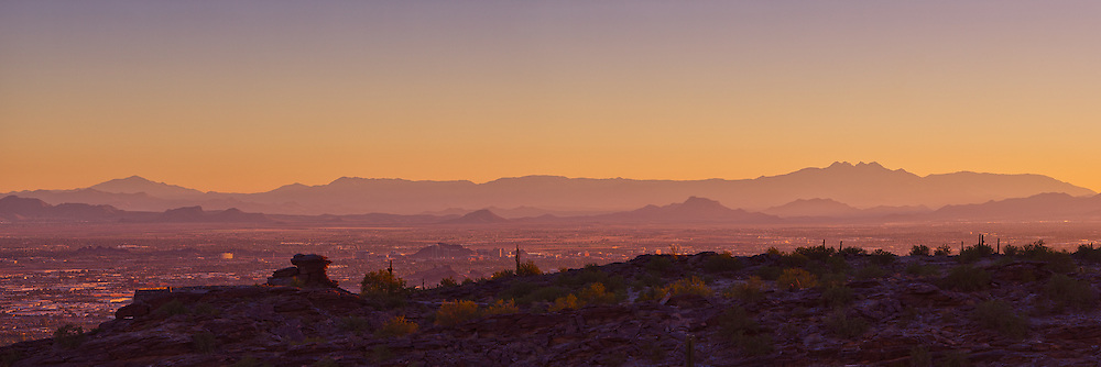 The sunrise silhouettes the distant mountain ridges over Scottsdale, Arizona. A great view from the South Mountain overlook near Phoenix.