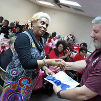Monroe County Extension Agent Randall Nevins shakes hands with Prairie RCDC President Dorothy Hale-Smith as she accepts the club's first-place ribbon at the annual Monroe County RCDC Banquet.