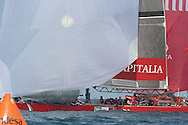 Italy's Capitalia foredeck crew stows genoa jib after hoisting spinnaker as they round mark during America's Cup fleet race; Valencia, Spain.