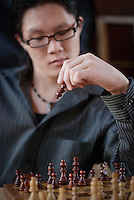 Asian male playing a game of chess.