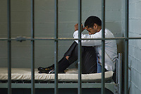 Mature man sitting on bed in prison cell