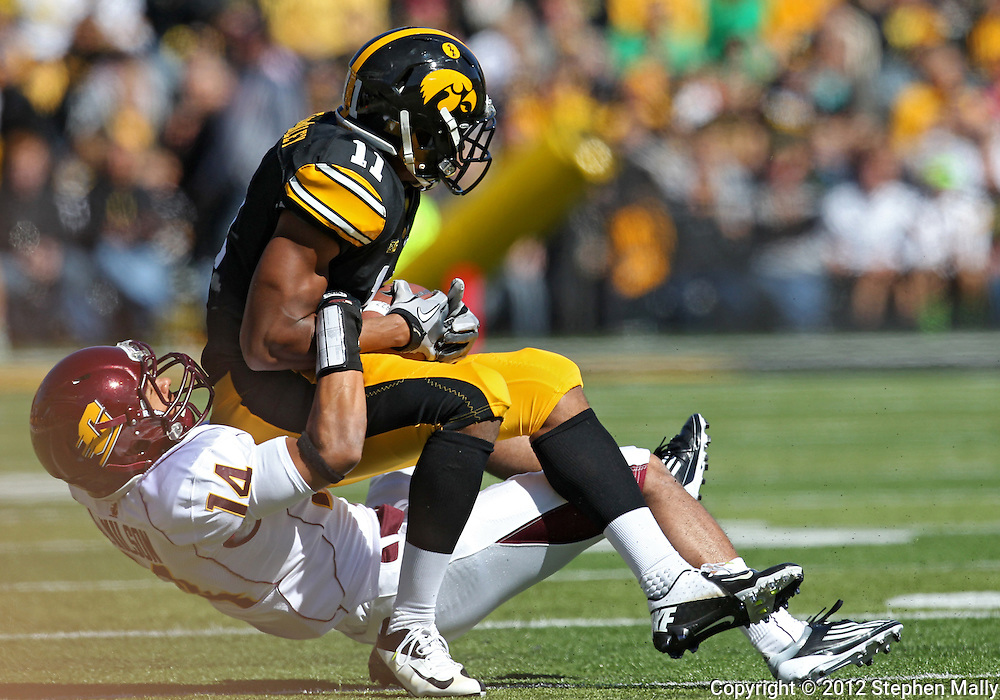 September 22 2012: Iowa Hawkeyes wide receiver Kevonte Martin-Manley (11) is pulled down by Central Michigan Chippewas defensive back Jason Wilson (14) after a catch during the first half of the NCAA football game between the Central Michigan Chippewas and the Iowa Hawkeyes at Kinnick Stadium in Iowa City, Iowa on Saturday September 22, 2012. Central Michigan defeated Iowa 32-31.