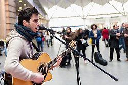 © Licensed to London News Pictures. 16/03/2016. London, UK. Luca Fiore (last year's GIGS winner) performs.  Buskers and street performers entertain morning commuters in King's Cross station, as this year's Busk in London programme is launched.  Supported by the Mayor of London, the festival joins the International Busking Day and National Busking Day initiatives to celebrate street performances. Photo credit : Stephen Chung/LNP