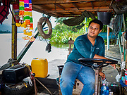 "09 JANUARY 2019 - KANCHANABURI, THAILAND: BOM, the operator of a small ferry on the River Kwai near Kanchanaburi. The ferry goes across the River Kwai downriver from downtown Kanchanaburi, the site of the famous ""Bridge on the River Kwai."" Small ferries like this, once common on Thai river crossings, are disappearing because Thailand has dramatically improved its infrastructure since this ferry started operating about 50 years ago. The ferry operator said his grandfather started the ferry, with a small raft he would pole across the river, in the late 1960s. Now his family has a metal boat with an inboard engine. There are large vehicle bridges across the river about 5 miles north and south of this ferry crossing, but for people in rural communities on the west side of the river the ferry is still the most convenient way to cross the river.      PHOTO BY JACK KURTZ"