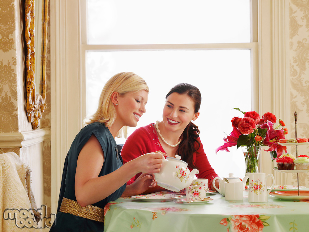 Two young women sitting at dining table pouring tea