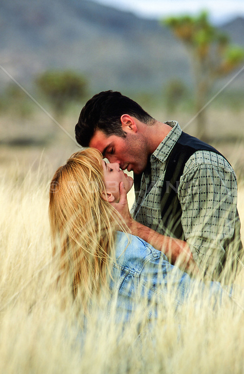 couple kissing in tall grass in the California Desert