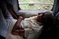 Pilgrim Jamnadas Prajapati aged 80 takes a nap as he travels for the 3rd time from Jhansi, Uttar Pradesh, to Kanyakumari to visit the Ramanathaswamy Temple. Jamnadas is a former railway employee and is allowed to travel with his wife, free of charge, to anywhere in India twice a year...Train passengers on the Himsagar Express 6318 going from Jammu Tawi station to Kanyakumari on 8th July 2009.. .6318 / Himsagar Express, India's longest single train journey, spanning 3720 kms, going from the mountains (Hima) to the seas (Sagar), from Jammu and Kashmir state of the Indian Himalayas to Kanyakumari, which is the southern most tip of India...Photo by Suzanne Lee / for The National
