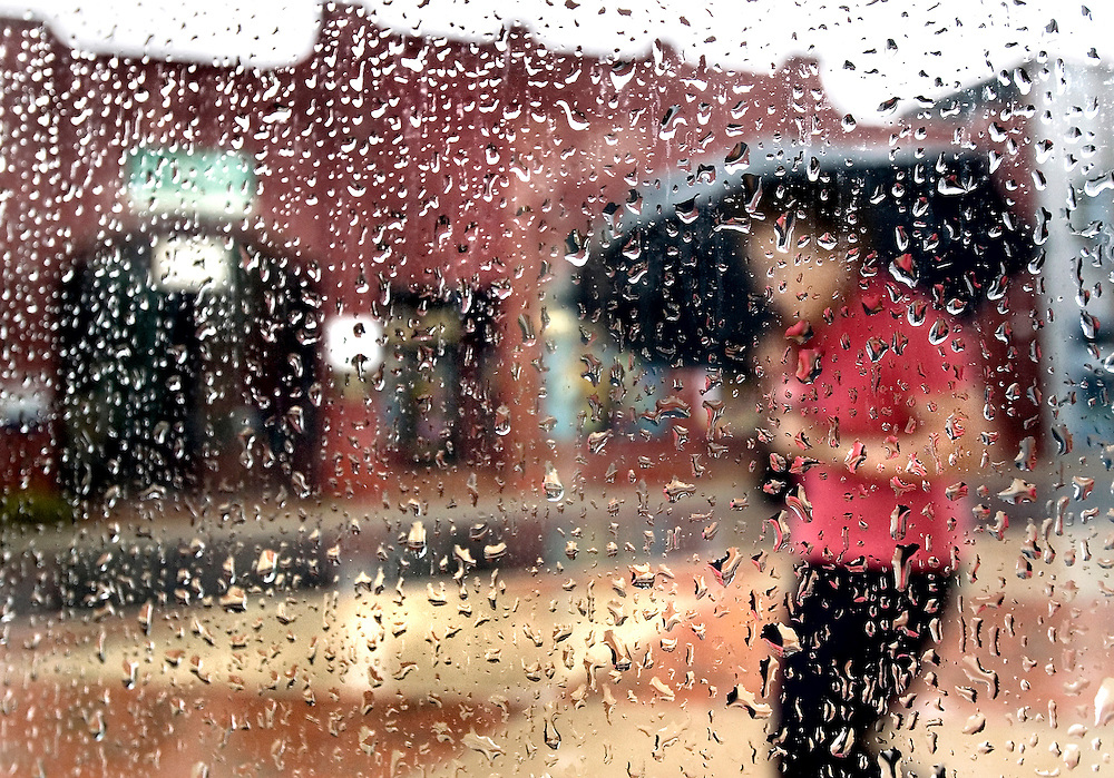 08/30/06-(Harrisonburg).A woman attempts to stay dry as she walks along South Main St. in Harrisonburg during a downpour on Wednesday afternoon..(Pete Marovich/Daily News-Record)