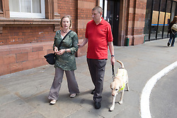 Vision impaired man with sighted guide and guide dog leaving a railway station