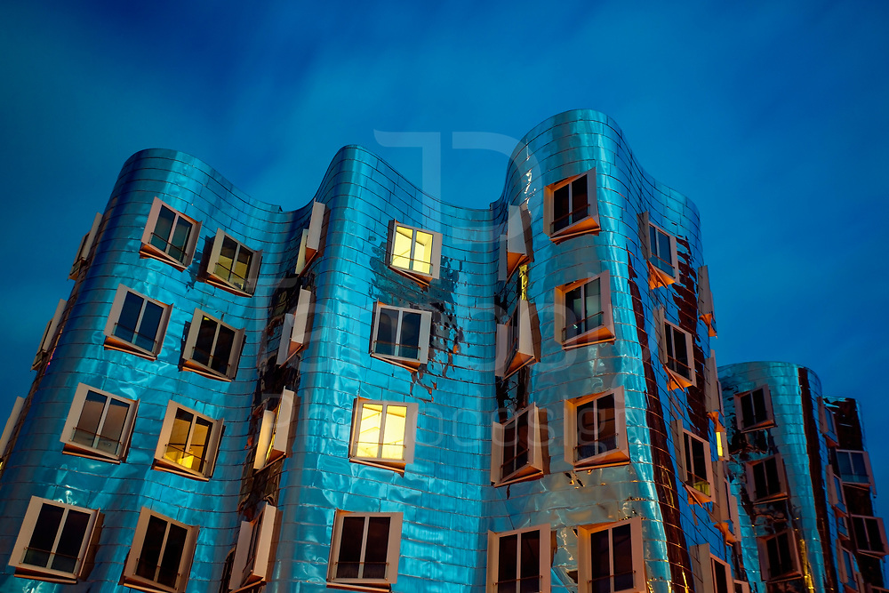 Illuminated facade of a Gehry House at the New Zollhof in Düsseldorf
