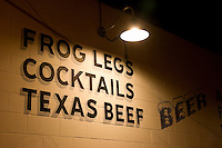 Restaurant sign offers frog legs and beef.