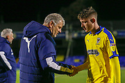 AFC Wimbledon midfielder Finlay Macnab (34) shakes the hand of AFC Wimbledon Manager Glyn Hughes after the EFL Trophy match between Southend United and AFC Wimbledon at Roots Hall, Southend, England on 13 November 2019.