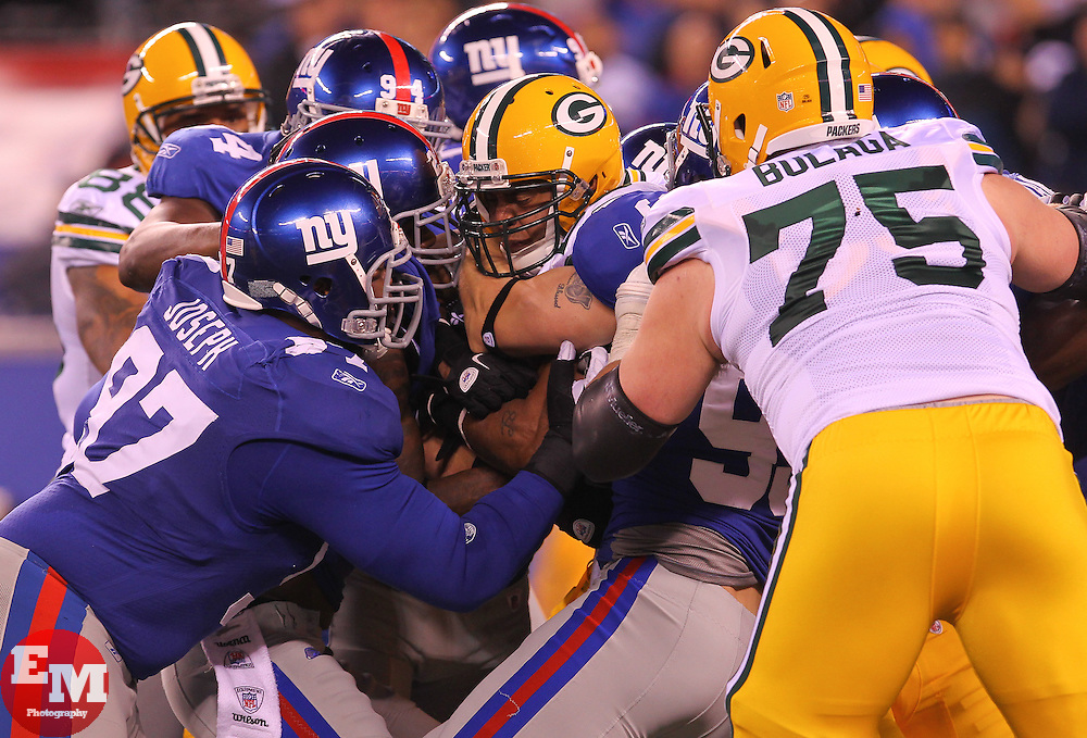 Dec 4, 2011; East Rutherford, NJ, USA; Green Bay Packers running back Ryan Grant (25) is tackled while running with the ball by New York Giants defensive tackle Linval Joseph (97) during the first half at MetLife Stadium.
