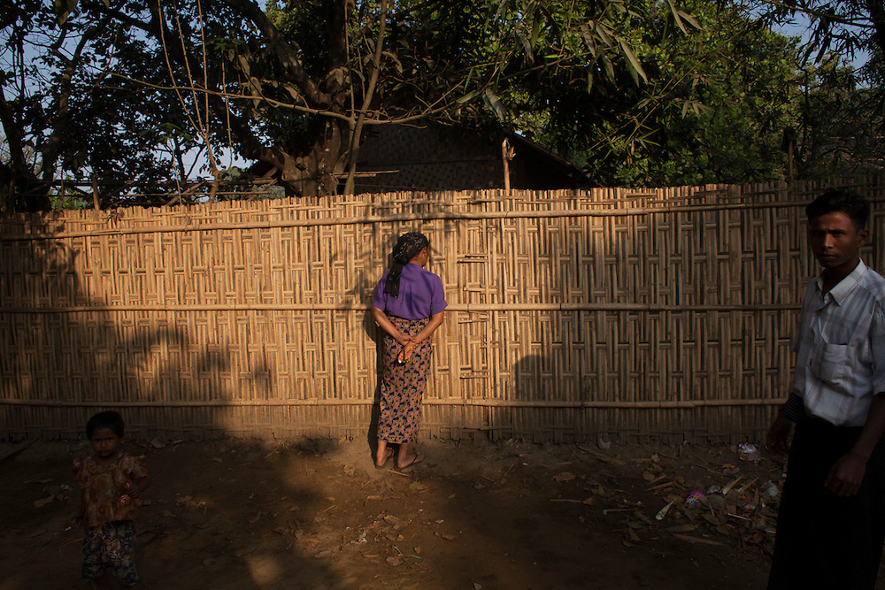 A Rohingya woman looks through a fence to observe people mourning after a man passed away in an IDP camp in Sittwe, Myanmar.