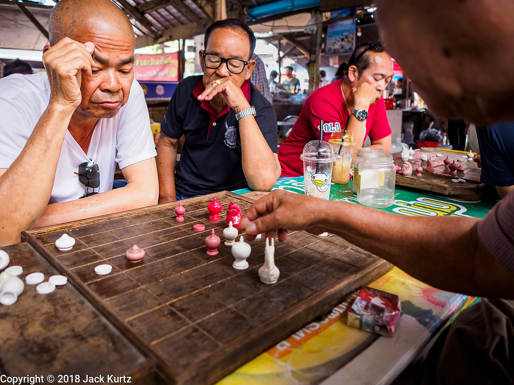 22 DECEMBER 2018 - CHANTABURI, THAILAND: Men play chess in a food stall in Chantaburi. Chantaburi is the capital city of Chantaburi province on the Chantaburi River. Because of its relatively well preserved tradition architecture and internationally famous gem market, Chantaburi is a popular weekend destination for Thai tourists.         PHOTO BY JACK KURTZ