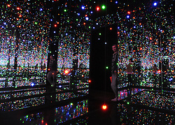 © Licensed to London News Pictures. 07/02/2012, London, UK. A man stands in 'Infinity Mirrored Room - Filled With The Brilliance of Life 2011. This is Kusama's largest mirrored room to date. Press preview of Yayoi Kusama at the Tate Gallery Bankside today 7th February 2012. The exhibition spans six decades of the artists work. Kusama is one of Japan's best known living artists.  Photo credit : Stephen Simpson/LNP